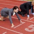 Businessman and woman on start line of running track — Stock Photo
