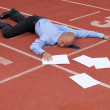 View of a businessman lying on a race track — Stock Photo