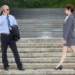 Businessman talking on phone while businesswoman walking on steps — Stock Photo