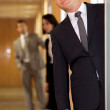 Businessman standing at door while colleagues in background — Stock Photo