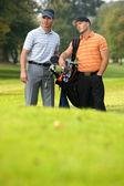 Unga män står på golfbanan bära väskor — Stockfoto