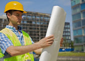 Engineer looking at blueprint on construction site — Stock Photo