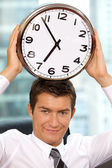 Portrait of smiling businessman holding clock to his head — Stock Photo
