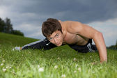 Young man exercising in park — Stock Photo