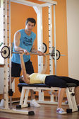 Young man helping a young woman lift a barbell on a bench — Stock Photo