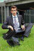 молодой кавказской бизнесмен, сидя на траве с документами — Стоковое фото
