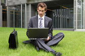 Young caucasian businessman sitting on grass using his laptop — Stock Photo