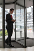 Young caucasian businessman at office revolving door with cellphone — Stock Photo