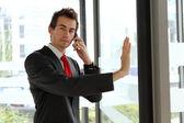 Giovane imprenditore caucasico presso ufficio porta girevole con cellulare — Foto Stock