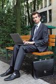 молодой кавказской бизнесмен, используя свой ноутбук в парке — Стоковое фото