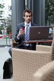 Young caucasian businessman using his laptop in cafe - drinking — Stock Photo