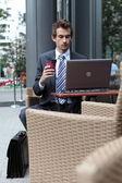 молодой кавказской бизнесмен, используя свой ноутбук в кафе - питьевой — Стоковое фото