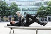 молодой кавказской бизнесмен, лежа на скамейке, читать газета — Стоковое фото