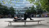 молодой кавказской бизнесмен, лежа на скамейке — Стоковое фото