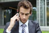 молодой кавказской бизнесмен, сидя на траве, говорить на сотовый телефон — Стоковое фото