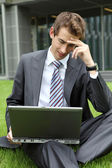 Young caucasian businessman sitting on grass reading bad news on laptop — Stock Photo