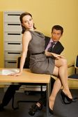 Businessman looking at woman sitting on table at office — Foto Stock