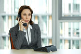 Portrait of young confident caucasian businesswoman talking on phone — Foto Stock