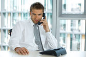 Portrait of young confident caucasian businessman talking on phone — Stock Photo