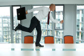 Young confident caucasian businessman running on the office table — Stock Photo