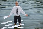 Portrait of businessman standing in lake with papers floating on water — Stock Photo