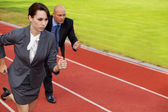 Businessman and woman on running on race track — Stock Photo