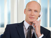 Portrait of businessman talking on telephone at office — Stock Photo