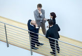 Businessmen and woman standing together by railing — Stock Photo