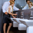 Young business couple flirting with each other at office washroom - Stock Photo
