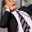 Businessman using telephone in office, smiling - Stock Photo