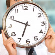 Portrait of businessman holding clock in office — Stock Photo