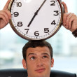 Businessman holding clock to his head — Stock Photo