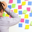 Businessman looking at wall of sticky notes with head in hands - Zdjęcie stockowe