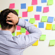 Businessman looking at wall of sticky notes with hands behind head — Stock fotografie