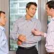 Foto Stock: Three businessmen discussing at office