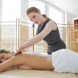 Portrait of young woman receiving massage from masseuse — Stock Photo #3840772