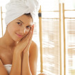 Stock Photo: Portrait of young womwrapped in towel with hands clasped