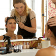 Female customer sitting in front of dressing table while beautician holding - Stock Photo