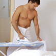 Man in towel ironing clothes on a stand — Stock Photo