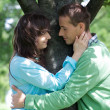 Young couple with arm around by tree — Stock Photo