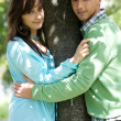 Young couple with arm around by tree — Stock Photo #3841548