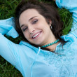 Portrait of young woman lying on grass — Stock Photo