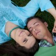 Portrait of young woman lying on grass with boyfriend — Stock Photo #3841683