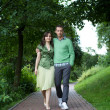 Young couple walking in park — Stock Photo