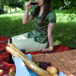 Young woman drinking wine in park — Stock Photo