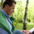 Young man reading book in park — Stock Photo