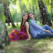 Young couple sitting back to back in park — Stock Photo #3842511