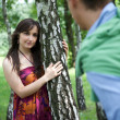 Stock Photo: Young couple standing in park by tree trunk