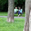 Young couple sitting on bench at park — Stock Photo