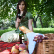 Low angle view of young woman holding wineglass, sitting in park — Stock Photo #3843825